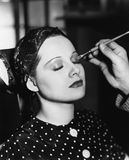 Young woman having make up done. (All persons depicted are no longer living and no estate exists. Supplier grants that there will be no model release issues Stock Images
