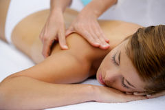 Young woman having a massage. Young topless woman lying down and having a massage Stock Images