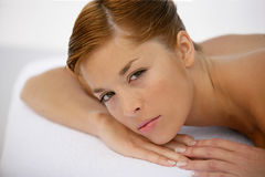 Young woman having a massage. Young woman lying down and having a massage Royalty Free Stock Image
