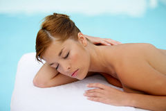 Young woman having a massage. Young woman lying down and having a massage Stock Image