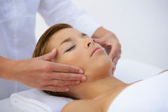 Young woman having a massage. Young woman lying down on her back and having a massage Stock Image