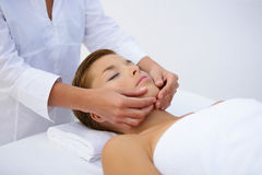 Young woman having a massage. Young woman lying down on her back and having a massage Stock Photography