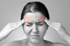 Young woman having migraine. A young woman holding her painful head Stock Photography