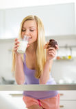 Young woman having muffin with milk in kitchen Royalty Free Stock Photography