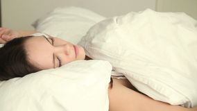 Young woman having nightmare. Young beautiful female having sleep problems, moving restless on bed, unable to fall asleep, having nightmare, lying with her eyes stock footage