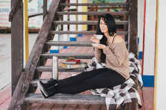 Young woman having picnic: drinking tea and reading book Stock Images