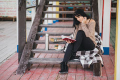 Young woman having picnic: drinking tea and reading book Stock Photos