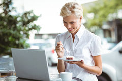 Young woman having a piece of pie using laptop Royalty Free Stock Image