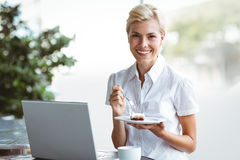 Young woman having a piece of pie using laptop Stock Images