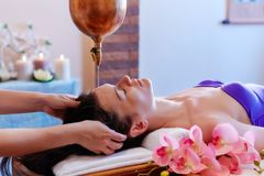 Young woman having pouring oil massage spa treatment. Shirodhar. A Pouring oil on head. Treatment of head stock photos