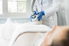 Woman having procedure of lipomassage. Young woman having procedure of lipomassage on legs in apparatus cosmetology clinic stock image