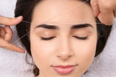 Young woman having professional eyebrow correction. Procedure in beauty salon, closeup royalty free stock images