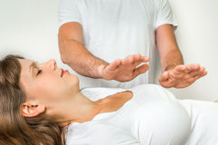 Young woman having reiki healing treatment Stock Images