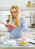 Young woman having snacks while studying Stock Images