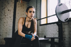 Young woman having some rest after hard workout in gym. Royalty Free Stock Photography