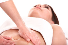 Young woman having stomach massage. Royalty Free Stock Image