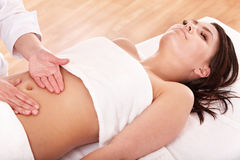 Young woman having stomach massage. Royalty Free Stock Photo