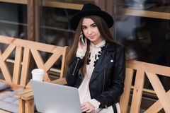 Young woman having telephone conversation while sitting with portable laptop computer in sidewalk cafe. Hipster girl dressed in classy clothes calling with cell Royalty Free Stock Image