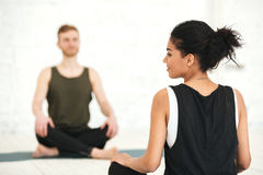 Young woman having a yoga class with male instructor stock photos