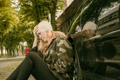 A young woman with head injury leans against a car. A young woman with a head injury leans against a car and looks painfully royalty free stock photography