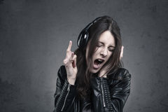Young Woman with head phones listening to music and Singing. Against dark wall background Stock Images