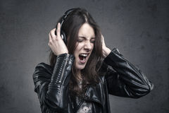Young Woman with head phones listening to music and Singing. Against dark wall background Stock Image