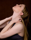 Young Woman With Head Tossed Back. A sensual portrait of a beautiful young woman tossing her head back and grasping her hair Stock Photo