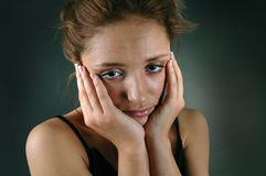 Young woman with headache. Beautiful young woman with a head ache, massaging her temples, looking sad stock images