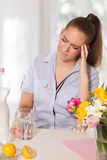 Young woman with headache holding a glass of water Stock Photo