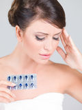 Young woman with a headache holding medication Royalty Free Stock Image