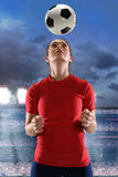 Young Woman Heading Soccer Ball Stock Image