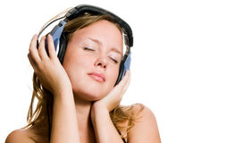 Young woman with headphones. Attractive young woman listing to music on headphones, white studio background Royalty Free Stock Image