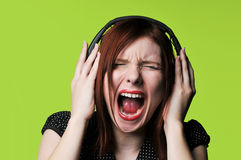 Young woman with headphones. Listening to loud music against a green background Stock Images