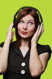 Young woman with headphones. Listening to loud music against a green background Royalty Free Stock Images