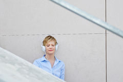 Young woman with headphones in city Royalty Free Stock Photography