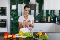 A young woman spends time at home, in the kitchen and in the roo. The young woman with headphones in the ears holding vegetables in hands in kitchen with laptop Royalty Free Stock Photos