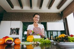 A young woman spends time at home, in the kitchen and in the roo. The young woman with headphones in the ears holding vegetables in hands in kitchen with laptop Royalty Free Stock Photography