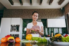 A young woman spends time at home, in the kitchen and in the roo. The young woman with headphones in the ears holding vegetables in hands in kitchen with laptop Royalty Free Stock Image