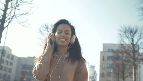 Young woman with headphones enjoying time in a city.