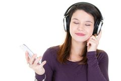 Young woman with headphones eyes closed and mobile phone. A young woman with headphones eyes closed and mobile phone stock image