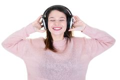 Young woman with headphones eyes closed in pink sweater. A young woman with headphones eyes closed in pink sweater stock image