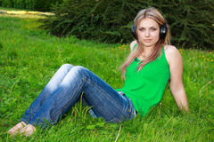 Young woman with headphones on grass Royalty Free Stock Photo
