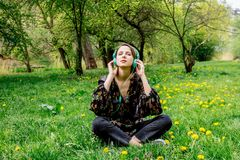 Young woman with headphones on green dandelion meadow in park.