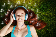 Young woman with headphones on green grass in park, music, infographic Royalty Free Stock Photos