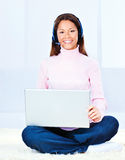 Young woman with headphones and laptop. Pretty young woman with headphones and laptop at home royalty free stock photos
