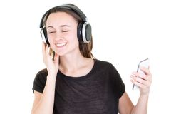 Young woman with headphones listen music from phone with eyes closed. A young woman with headphones listen music from phone with eyes closed stock photography