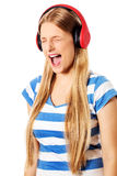 Young woman with headphones listening and singing to music, isolated on white Stock Photos