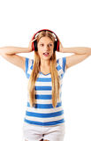 Young woman with headphones listening and singing to music, isolated on white Stock Photo