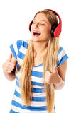 Young woman with headphones listening and singing to music, isolated on white Royalty Free Stock Images