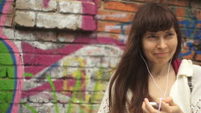 Young woman with headphones listening to music next to the wall with graffiti stock footage